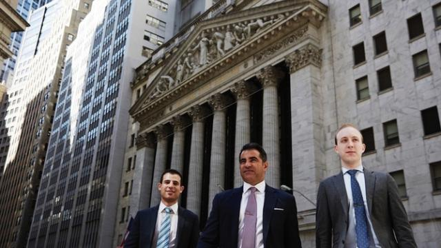 Three guys in front ofd Stock Exchange New York